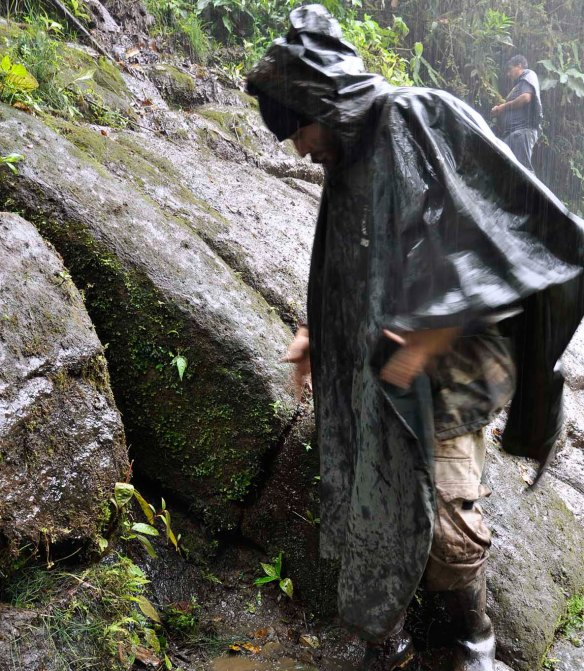 EcoMinga's Juan Pablo Reyes examines a cross-section of the wall. The stones are very thick. Photo:Lou Jost/EcoMinga.